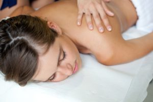 relaxed woman receiving massage therapy at a spa