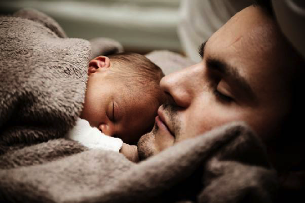 father sleeping with infant